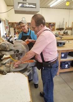 Hobby Shop volunteer, Susan, assists participant, John, with a woodworking project.